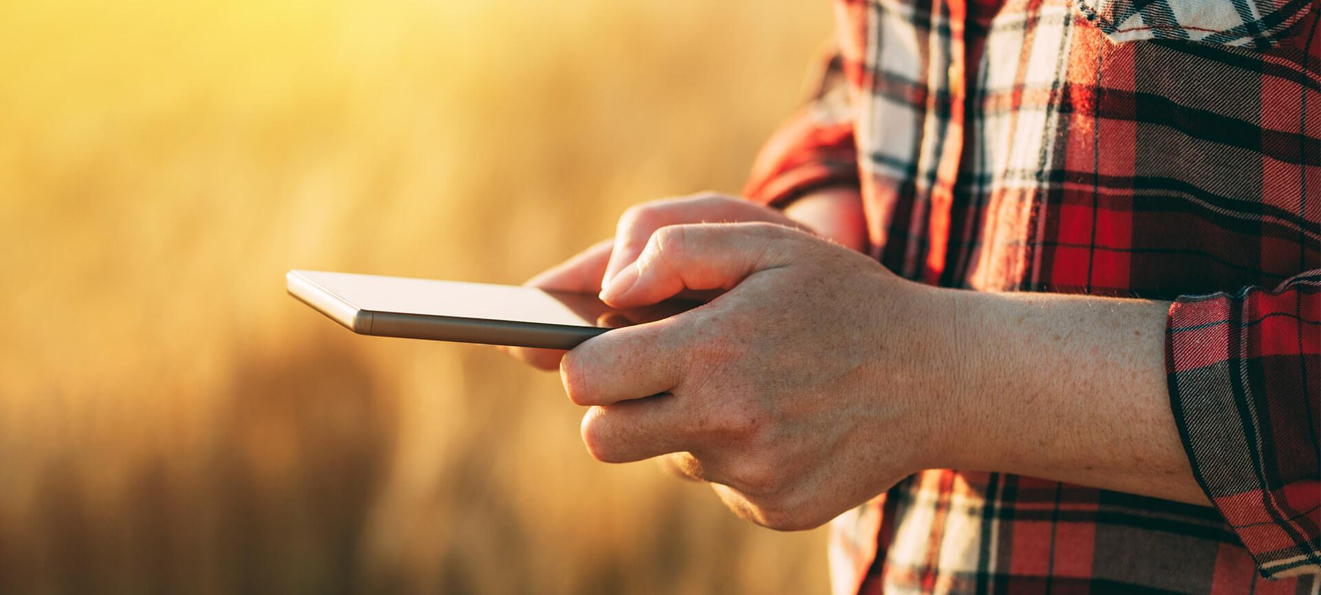 Close up of farmer using phone in a field