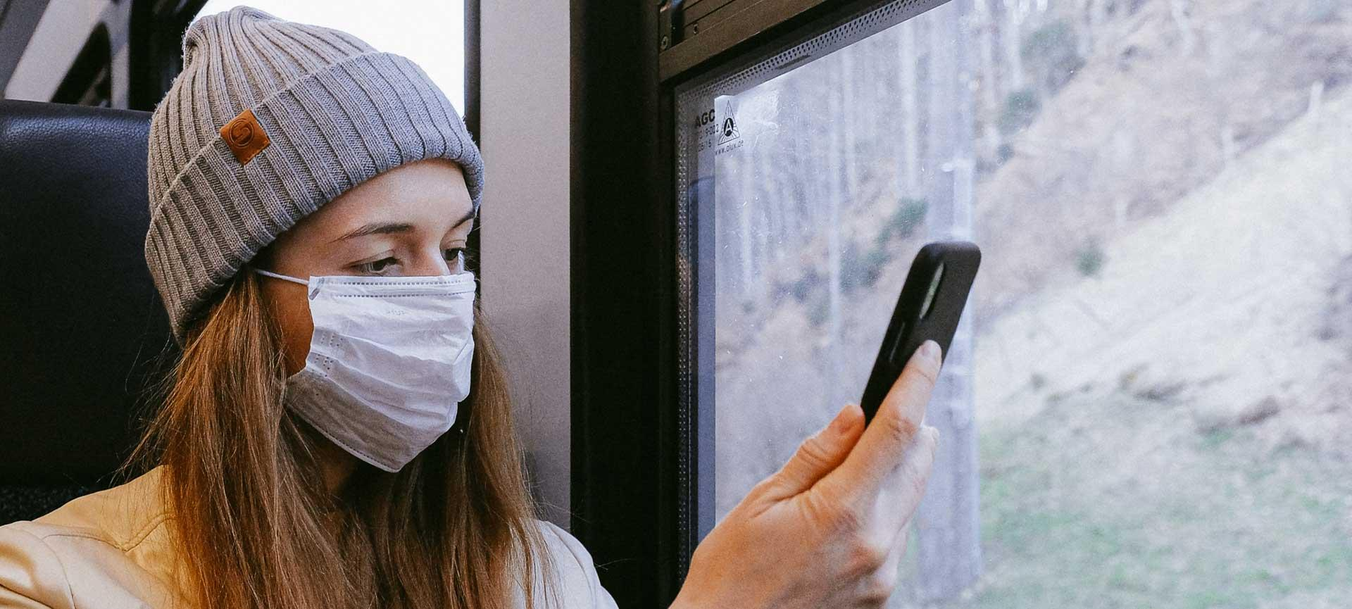 Woman wearing face mask using phone