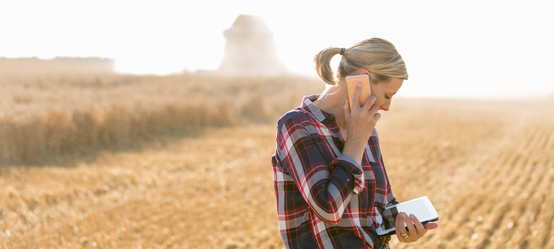 Woman standing in dry field looking at ipad and speaking on mobile phone