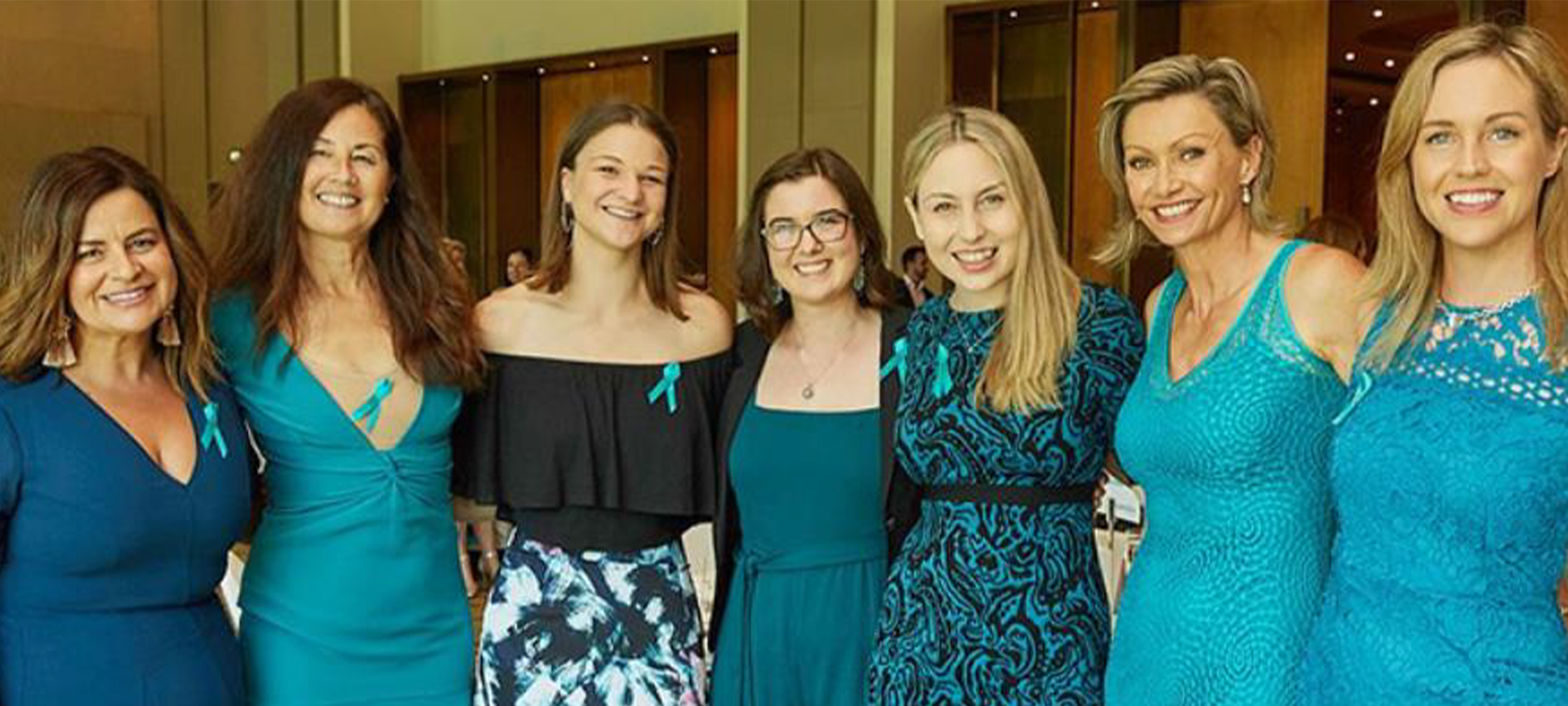 Seven women standing in a row, arms around each other, wearing blue outfits