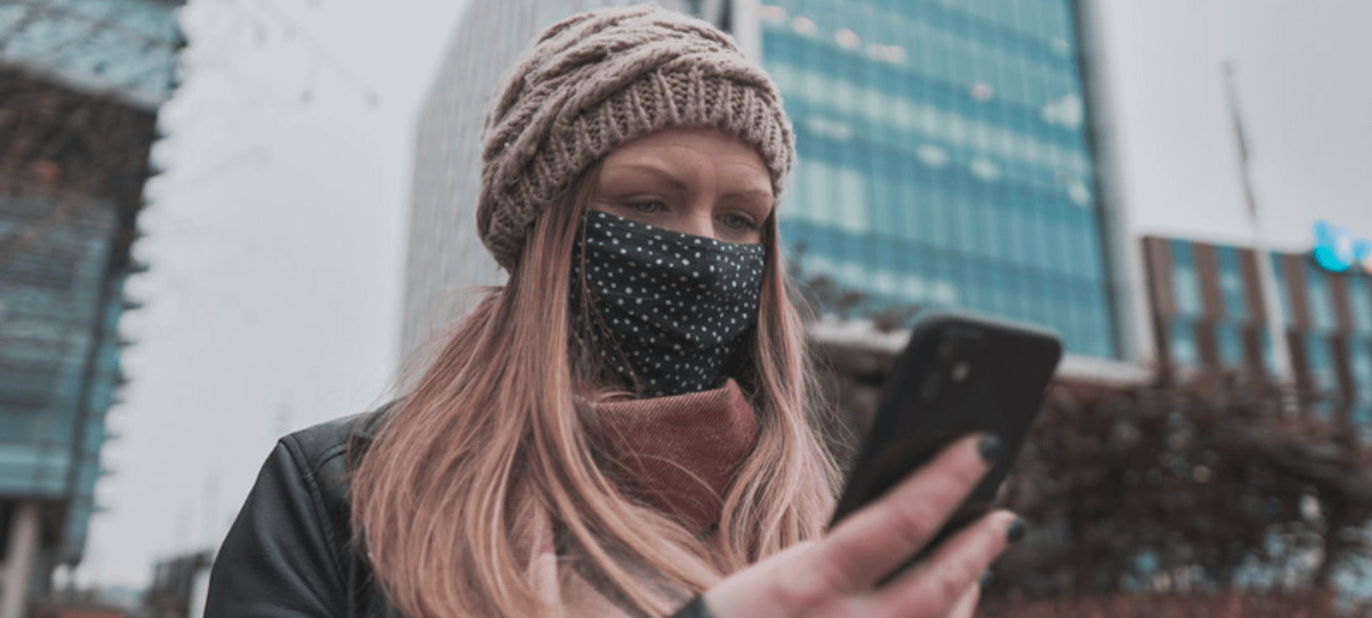 woman wearing face mask and beanie, looking at her phone