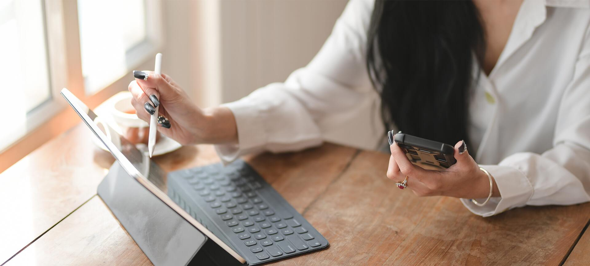 Woman working from home with tablet and phone