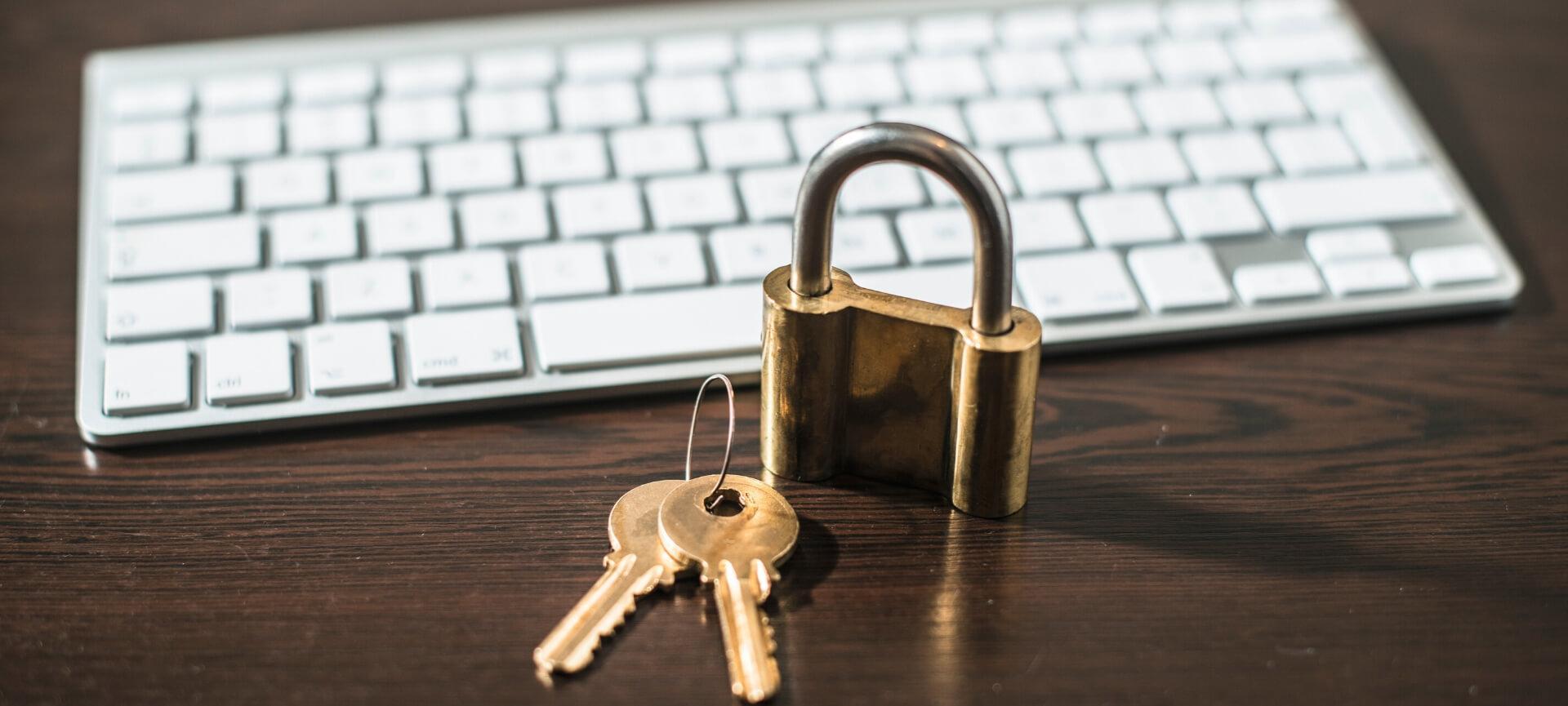 Padlock and key next to keyboard