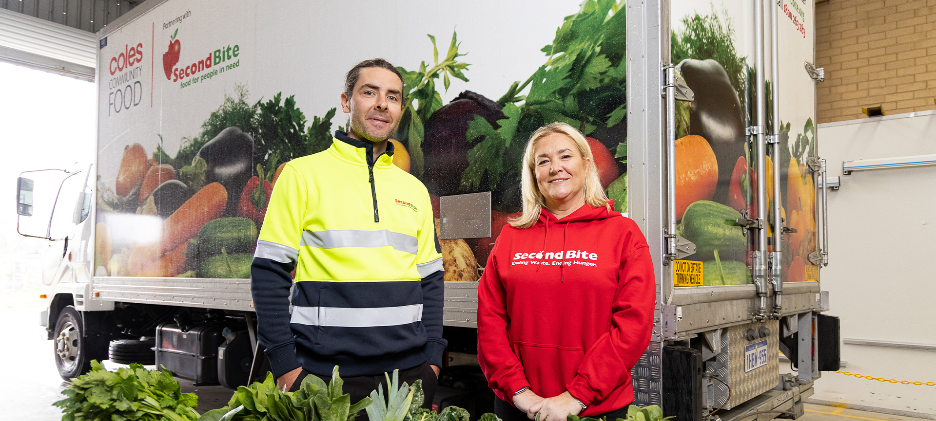 Zoe Fulcher in red jumper standing with Lyndon in high vis in front of the SecondBite truck