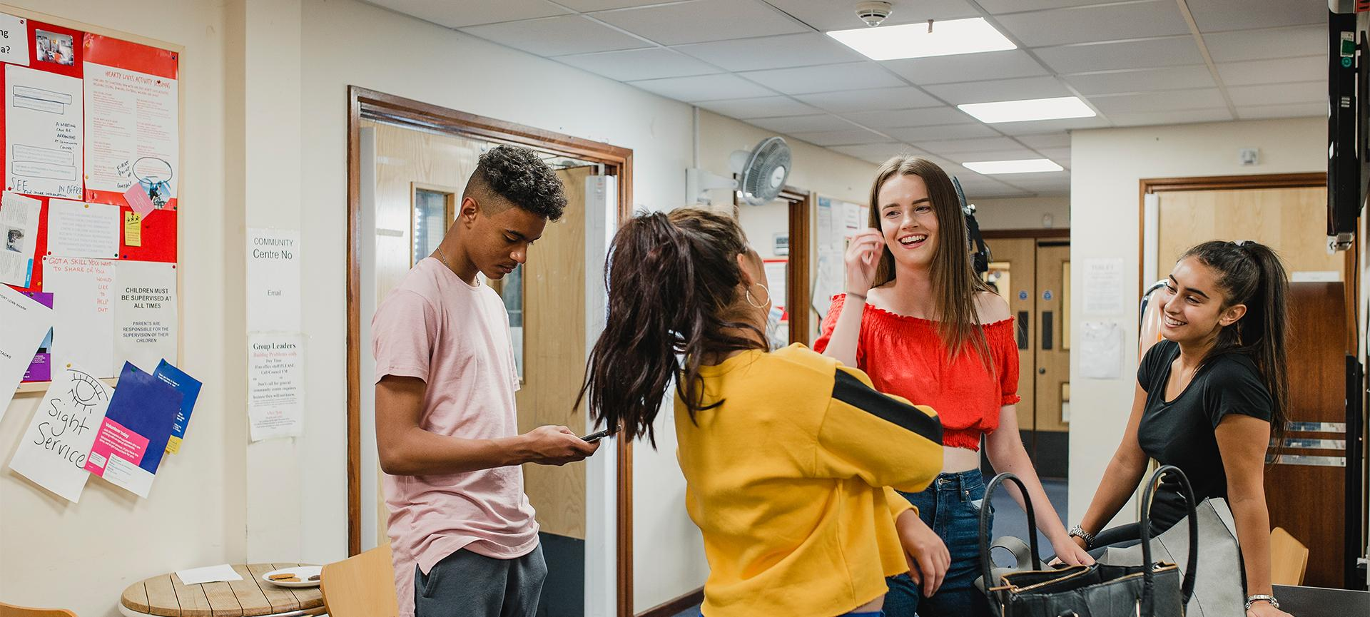 Four teenagers hanging out talking and smiling in a youth centre