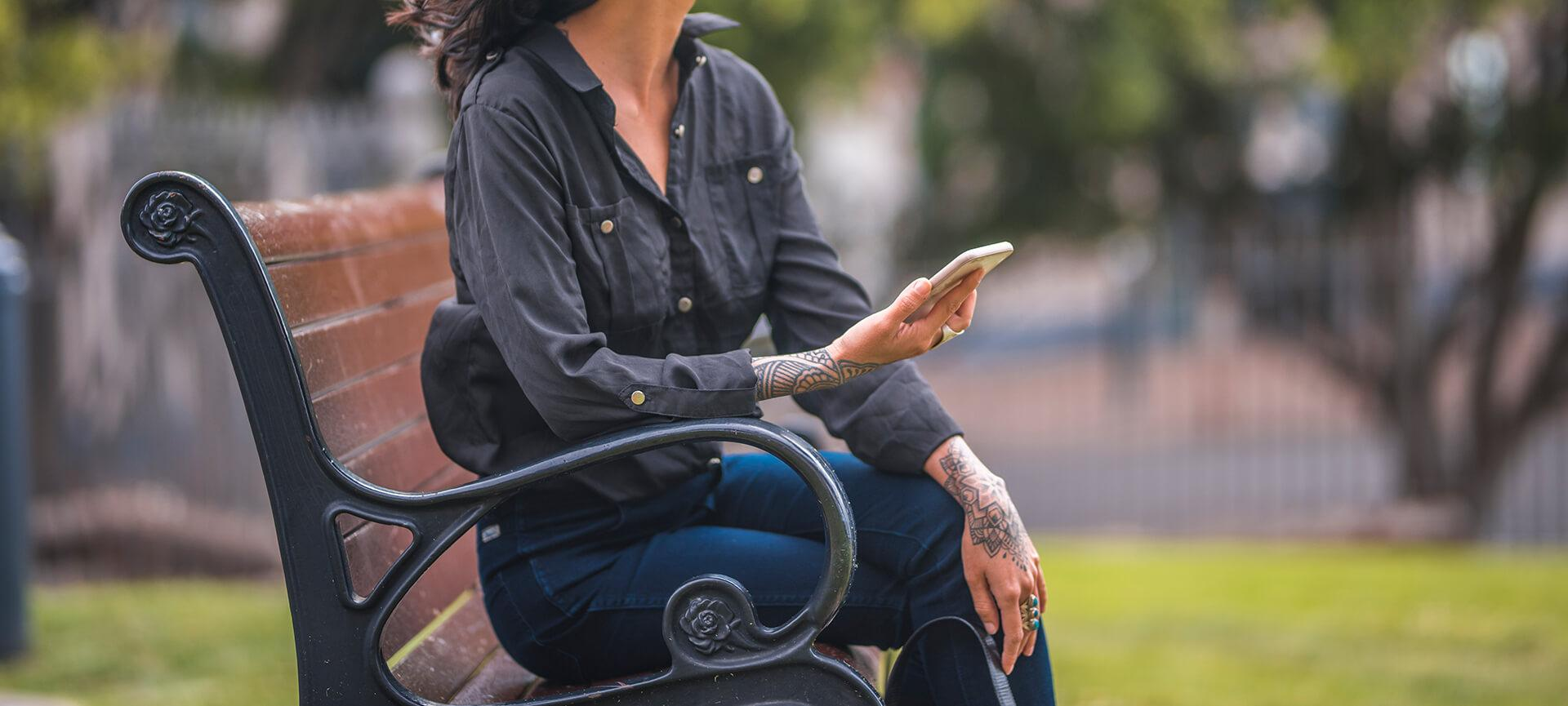 Close up of woman holding phone on park bench