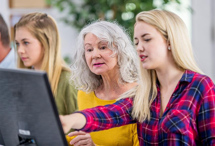 Older woman using computer with help from younger woman