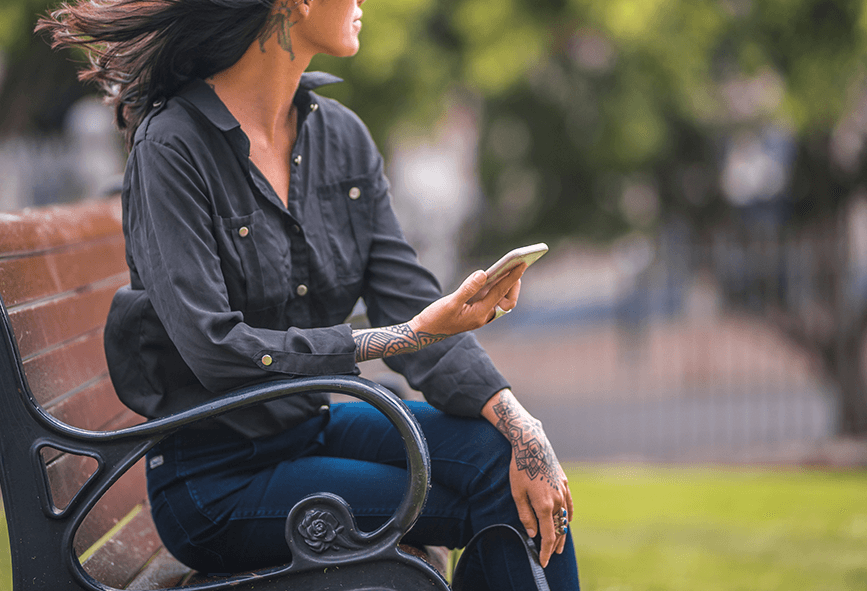 Woman holding phone on park bench