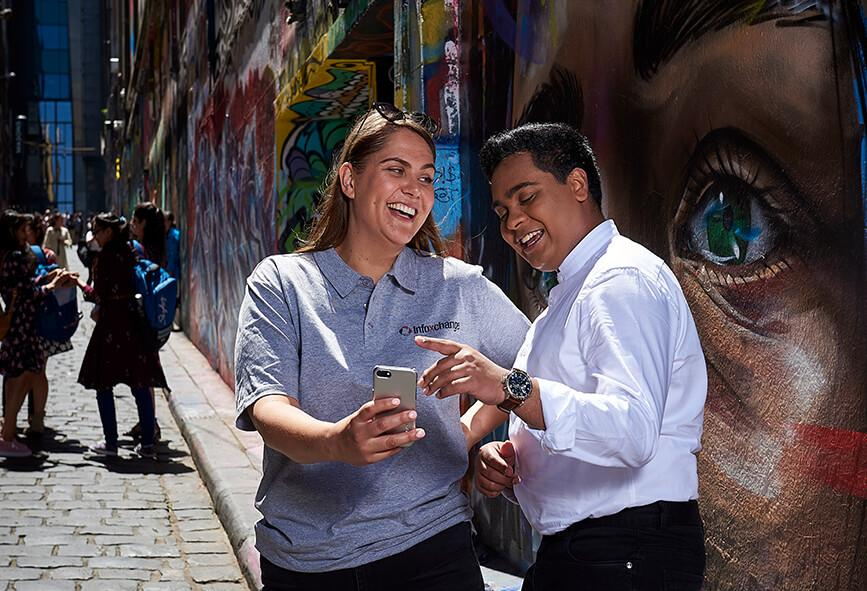 Two people looking at a smart phone in an urban street scene