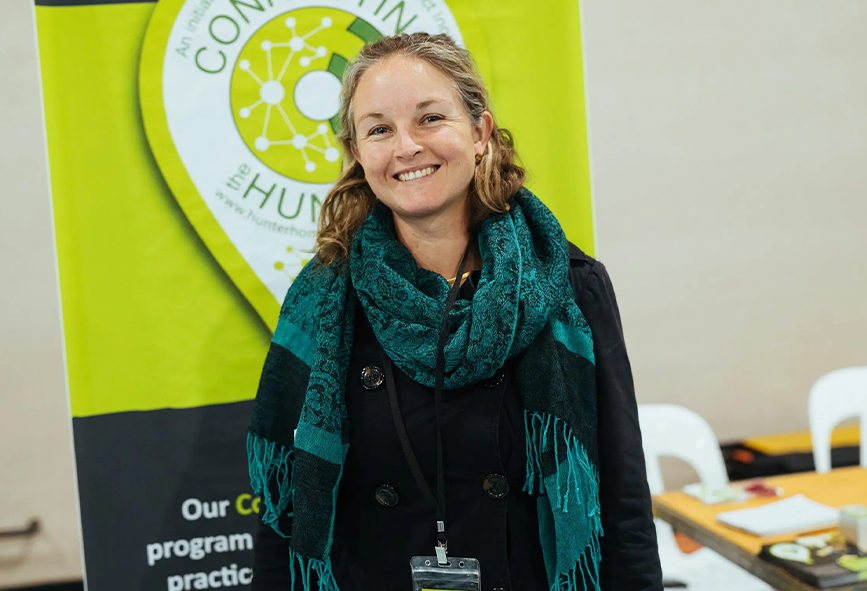 Nissa Phillips standing in front of green Hunter Homeless Connect sign
