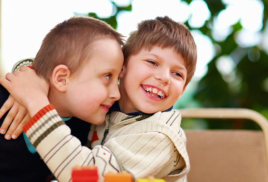 Boys with disability hugging and smiling