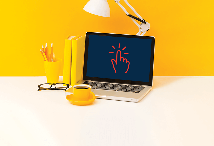 Laptop on desk with bright yellow background