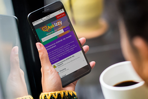 Ask Izzy on mobile screen held by woman with coffee