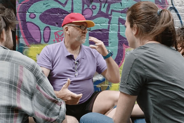 man_talking_to_youth_in_front_of_graffiti.jpg