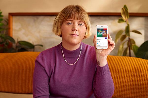 Nellie Jackson holding phone showing Ask Izzy